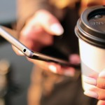 Person with cellphone and coffee